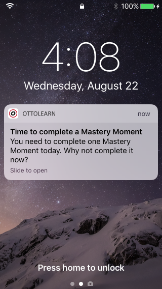 """Push notification that would appear on a mobile device. The device's lock screen is shown with a notification sent from OttoLearn. The text in the notification reads """"Time to complete a Mastery Moment. You need to complete one Mastery Moment today. Why not complete it now? Slide to open."""