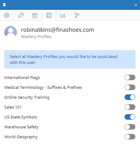 """The Assign Mastery Profiles tab of the user context panel for a user named Robin Atkins. In the tab, there is a message at the top that reads: """"Select all Mastery Profiles you would like to be associated with this user."""" Several Mastery Profiles are listed below, each with a toggle on the right side. Some toggles are on (Mastery Profile assigned) and some are off."""