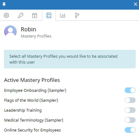 "The Assign Mastery Profiles tab of the user context panel for a user named Robin Atkins. In the tab, there is a message at the top that reads: ""Select all Mastery Profiles you would like to be associated with this user."" Several Mastery Profiles are listed below, each with a toggle on the right side. Some toggles are on (Mastery Profile assigned) and some are off."